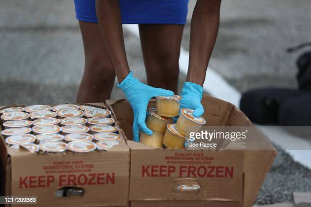 City of Sunrise employee places groceries provided by the food bank Feeding South Florida into the vehicles of the needy on April 06 2020 in Sunrise...