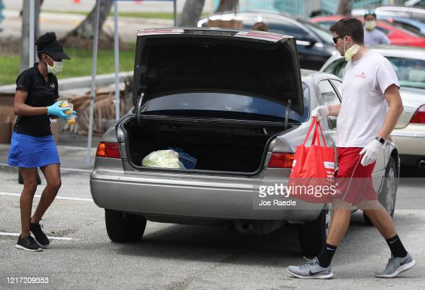 City of Sunrise employees place groceries provided by the food bank Feeding South Florida into the vehicles of the needy on April 06 2020 in Sunrise...