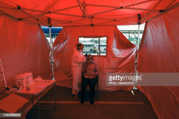 City of Tshwane Healthcare official takes a throat swab to test for the COVID-19 coronavirus on a woman at the Denlyn Mall taxi rank in Mamelodi...