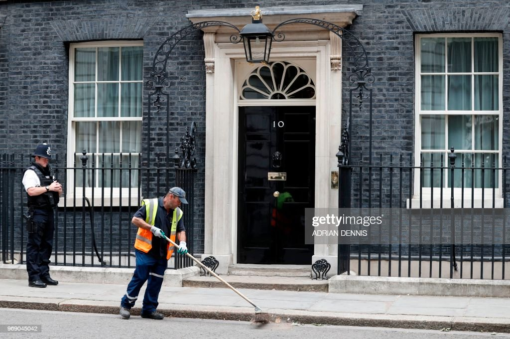A City of Westminster worker sweeps rubbish from the street outside the door to 10 Downing Street in London on June 7, 2018. - British Prime Minister Theresa May is set to gather her ministers Thursday amid swirling rumours that Brexit secretary David Davis could quit over her plans to avoid a hard Irish border.