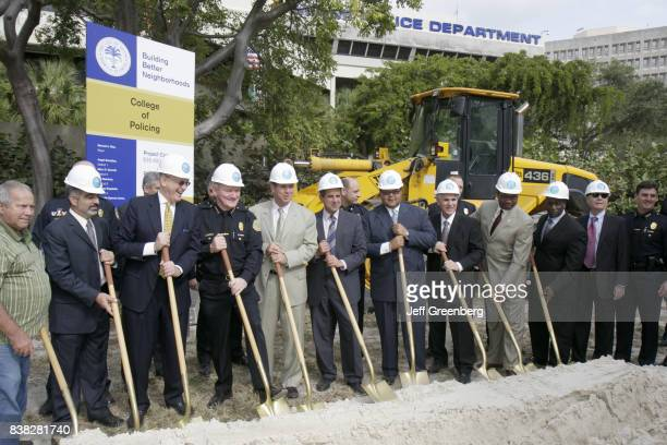 City officials and politicians wearing hard hats and holding shovels at the groundbreaking ceremony for the College of Policing