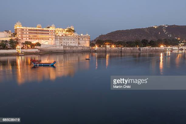 City Palace in Udaipur at night, reflected in Lake Pichola