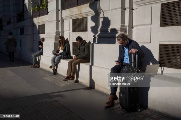 City people check for messages and use social media in the street sitting in autumn sunshine on 27th October 2017 in the City of London England