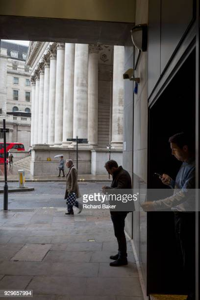 City people shelter from rain in the privacy of a dark corner to check messages by Cornhill in the City of London the capital's financial district...