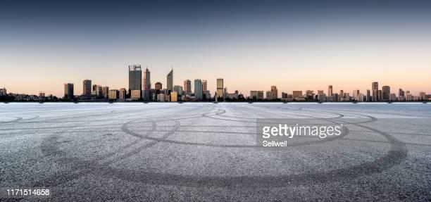 city road against perth urban skyline, during sunset - perth australien stock-fotos und bilder