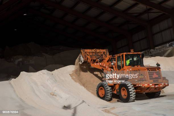 A city sanitation worker uses a backhoe to pile up road salt at a storage depot on the Lower East Side January 3 2018 in New York City New York City...