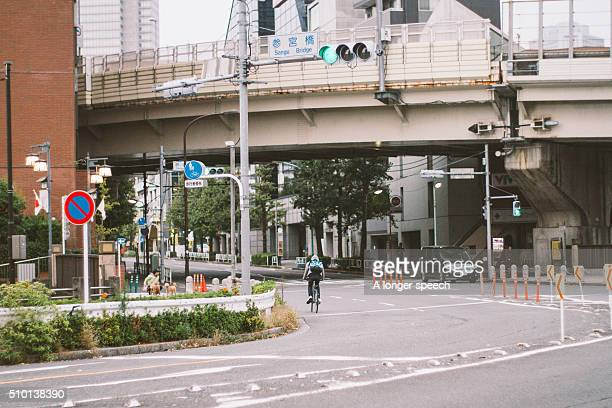 A city scape of Tokyo with a young man riding his bicycle