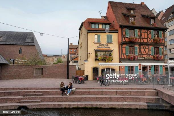 city scene by the canal with people sitting on steps and sidewalk cafes,colmar. - emreturanphoto stock pictures, royalty-free photos & images