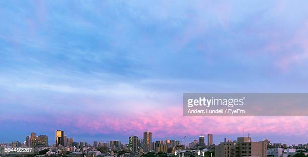 City Skyline Against Cloudy Sky During Sunset
