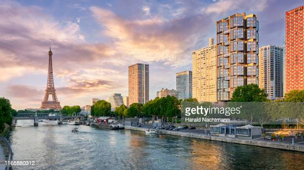 city skyline along seine river with eiffel tower and highrise buildings at front de seine, paris, france - jour photos et images de collection