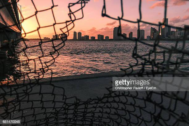 City Skyline And Sea Against Sky Seen From Broken Chainlink Fence