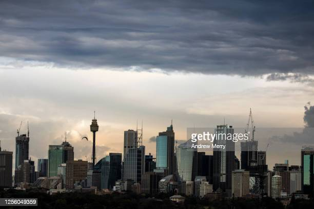 city skyline and storm clouds at dusk - wet stock pictures, royalty-free photos & images