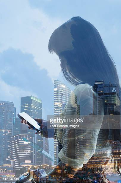 City skyline and young woman using smartphone, reflection on window