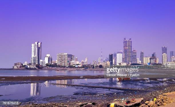 City Skyline By River Against Clear Sky