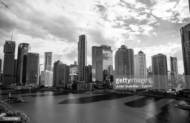 City Skyline By River Against Cloudy Sky