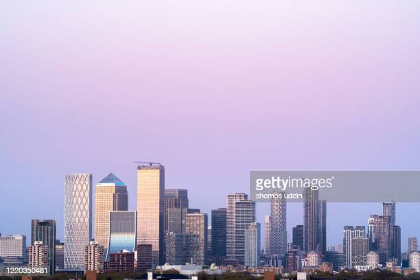city skyline of london canary wharf at dusk - clear sky stock pictures, royalty-free photos & images