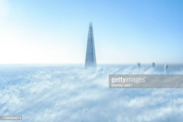 city skyline of london emerging through clouds - appearance stock pictures, royalty-free photos & images