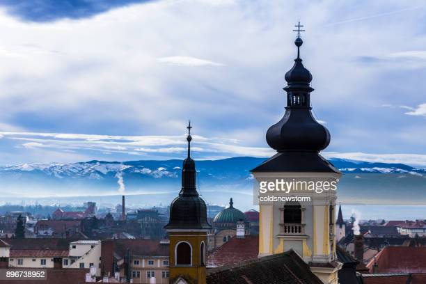 City skyline of Sibiu, Transylvania, Romania with church spires and snowy Carpathian mountains in distance