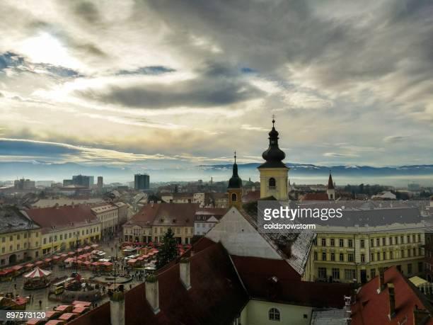 skyline der stadt von sibiu, siebenbürgen, rumänien mit kirchtürmen und verschneiten karpaten in ferne - sibiu stock-fotos und bilder