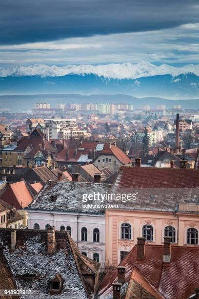 die skyline der stadt von sibiu, siebenbürgen, rumänien mit schnee bedeckt karpaten in ferne - sibiu stock-fotos und bilder