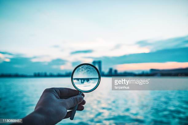 city skyline reflected in a magnifying glass - magnifying glass stock pictures, royalty-free photos & images
