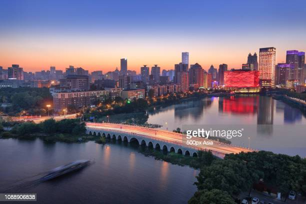 city skyline with han show theatre at dusk, wuhan, hubei, china - wuhan stock photos and pictures