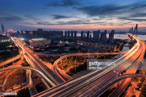 city skyline with ring road viaduct at dusk, wuhan, hubei, china - wuhan city stock photos and pictures