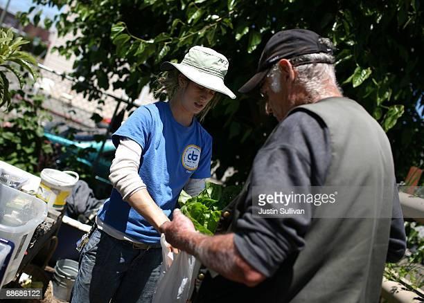 City Slicker Farms gardener apprentice Adelle Martin gives freshly harvested vegetables to a neighborhood resident at the Center Street Farm June 25...