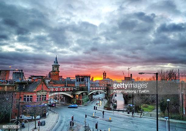 city street against sky during sunset - manchester england stock pictures, royalty-free photos & images