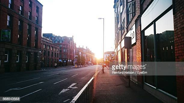city street amidst buildings against clear sky during sunset - manchester uk stock photos and pictures