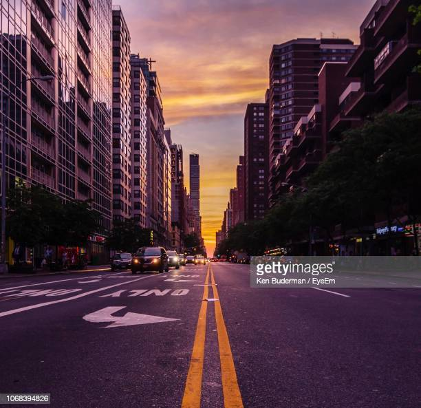 city street amidst buildings against sky during sunset - dividing line road marking stock pictures, royalty-free photos & images