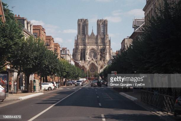 city street amidst buildings against sky - reims stock pictures, royalty-free photos & images