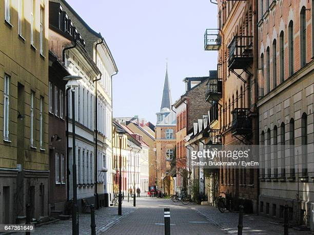 city street amidst buildings by church against clear sky - malmo stock pictures, royalty-free photos & images