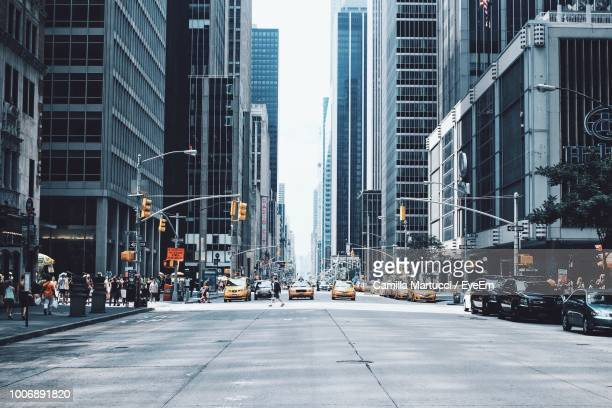 city street amidst buildings - new york city stock-fotos und bilder