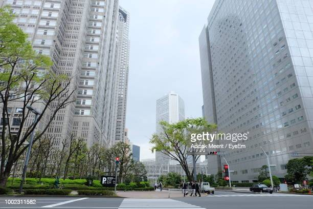 city street and buildings against sky - オフィス街 ストックフォトと画像