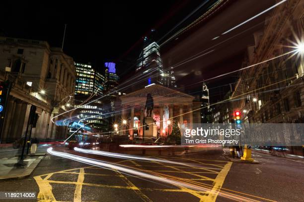 city street and junction at night with traffic and light trails, london. uk - atmospheric mood stock pictures, royalty-free photos & images