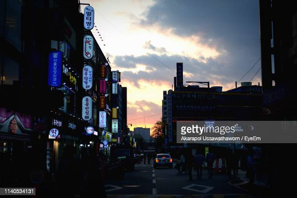 city street and silhouette buildings against cloudy sky at night - daejeon stockfoto's en -beelden