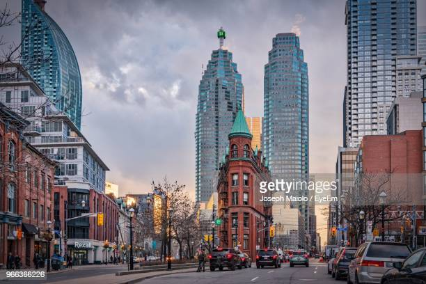 city street by buildings against sky - toronto stock pictures, royalty-free photos & images