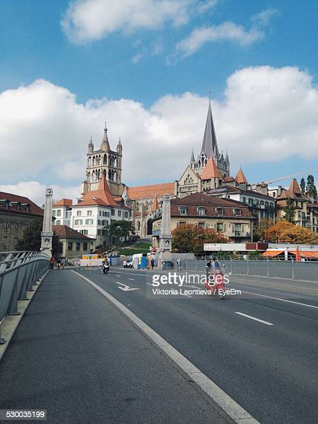 city street by church against sky - lausanne stock pictures, royalty-free photos & images