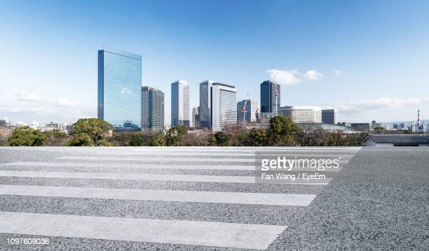 city street by modern buildings against sky - 金融街 ストックフォトと画像