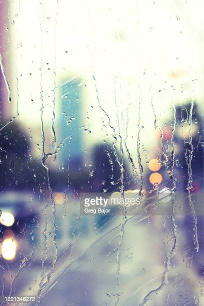 city street viewed through rain covered window - greg bajor stock pictures, royalty-free photos & images