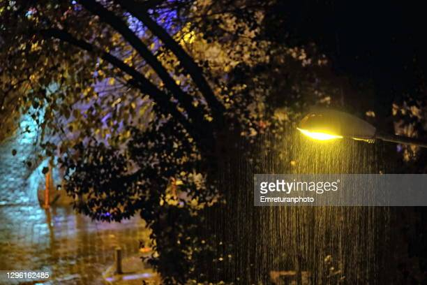 city street with lamp under rain at night. - emreturanphoto fotografías e imágenes de stock