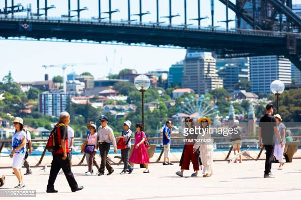 city street with tourists and holiday makers enjoying suny day - tourist stock pictures, royalty-free photos & images