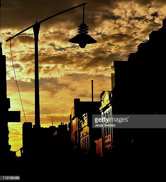 City sunrise with street lamp and clouds