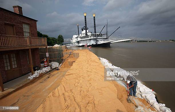 City surveyor Tony Moon works on a makeshift levee on the edge of the flooding Mississippi River with the temporarily shuttered Isle of Capri...