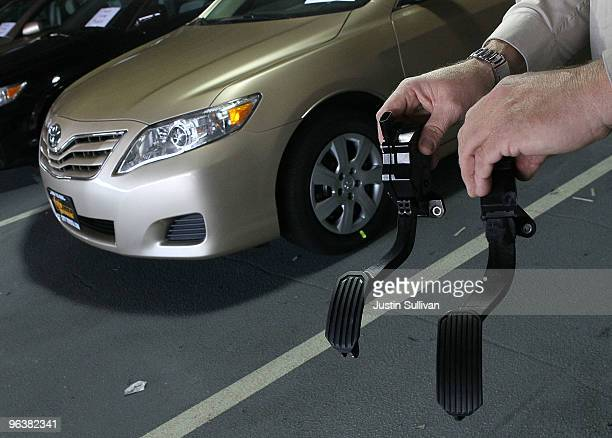 City Toyota service manager Jim Lasseter holds a recalled accelerator pedal and the new modified part next to a brand new Toyota Camry that is...