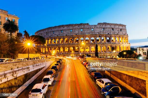 city traffic and illuminated coliseum at night, high angle view, rome, italy - monumento foto e immagini stock
