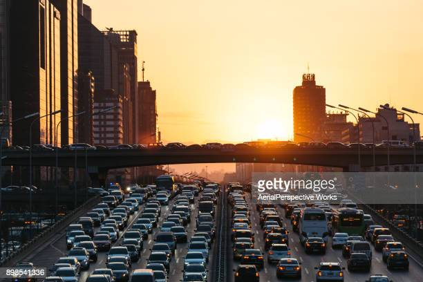 city traffic jam at sunset - traffico foto e immagini stock