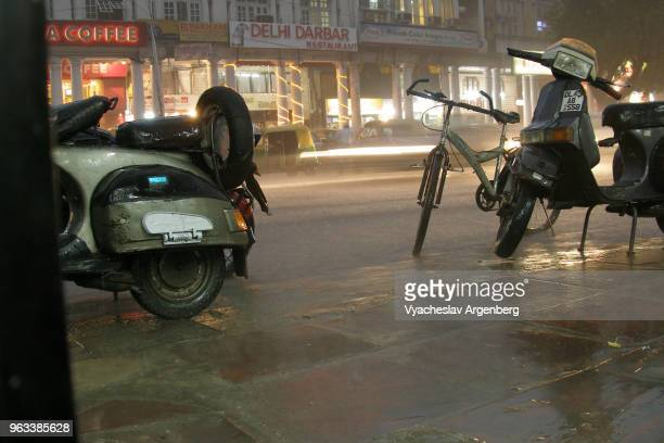 city traffic on the street, motorcycles under the rain, night time at connaught place, new delhi, india - argenberg fotografías e imágenes de stock