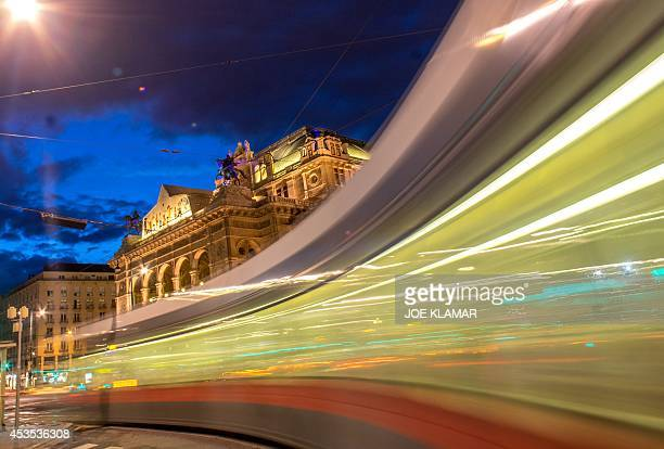 A city tram makes a turn in front of the litup Wiener Staatsoper Vienna's State Opera building during the twilight in the city center of Vienna on...